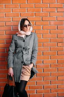 Młoda i piękna kobieta, pozowanie na ścianie z czerwonej cegły