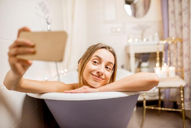 Młoda i piękna kobieta robi zdjęcie selfie z telefonem leżącym w wannie retro w pomieszczeniu