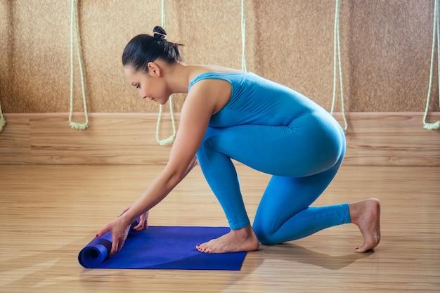 Młoda i piękna kobieta rozkłada matę treningową do jogi na drewnianej podłodze. fioletowa mata w rękach kobiety. koncepcja koncentracji i praktyki jogi
