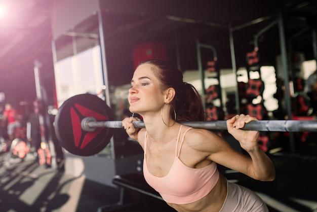 Młoda i piękna kobieta trenuje ze sztangą na siłowni. pozowanie z elementami do treningu