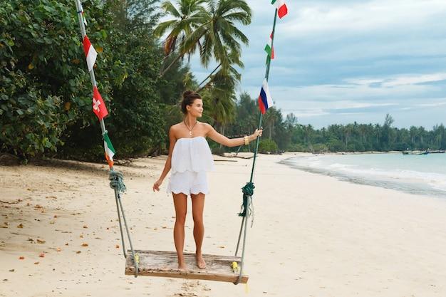 Młoda i piękna kobieta ubrana w biały kombinezon na huśtawkach na plaży