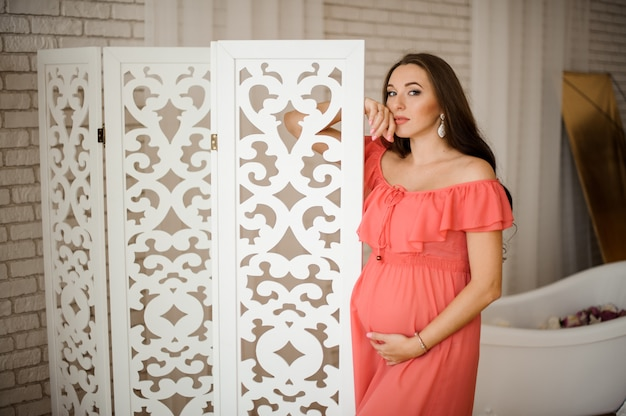 Młoda i piękna kobieta w ciąży w długiej sukni
