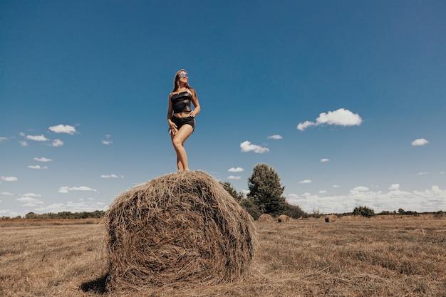 Młoda i piękna kobieta wypoczywa samotnie na łonie natury w upalny letni dzień na stogu siana