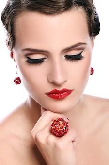 Młoda i piękna kobieta z czerwoną biżuterią