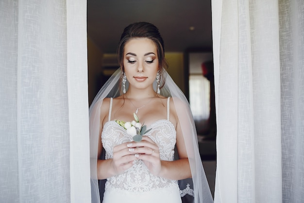Młoda i piękna panna młoda stoi blisko okno z kwiatami w domu