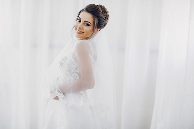Młoda i piękna panna młoda w domu idzie na wesele