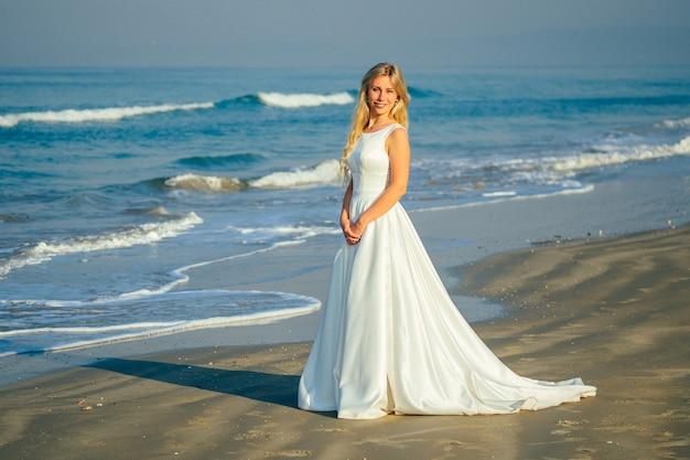 Młoda i piękna panna młoda z długimi blond włosami pięknie uśmiechnięta i chodzenie po morzu w pięknej białej sukni ślubnej długiej. szczęśliwa panna młoda poślubiła ceremonię ślubną na plaży nad morzem