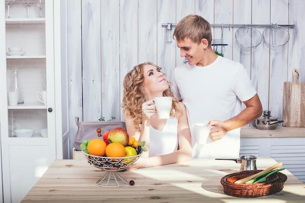 Młoda i piękna para w kuchni w domu gotuje i je śniadanie razem, pomagając sobie nawzajem