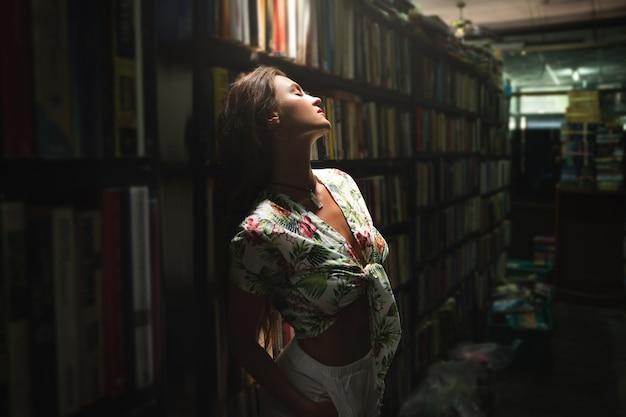 Młoda i seksowna kobieta w księgarni vintage