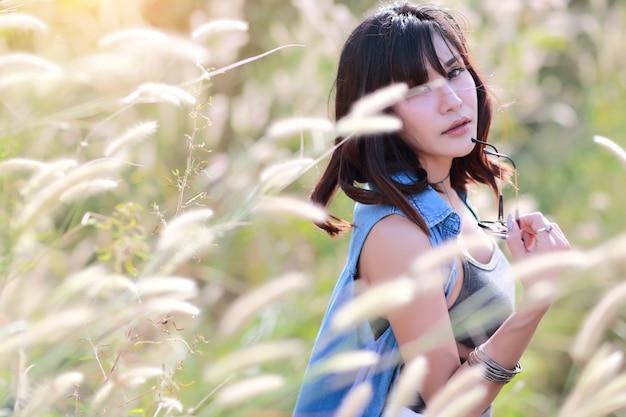 Młoda i śliczna dziewczyna ma szczęśliwego czas i cieszy się wśród trawy pola w naturze