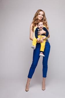 Młoda i sprawna kobieta w ubranie gospodarstwa małe dziecko.