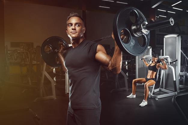 Młoda i sprawna para na siłowni robi treningu