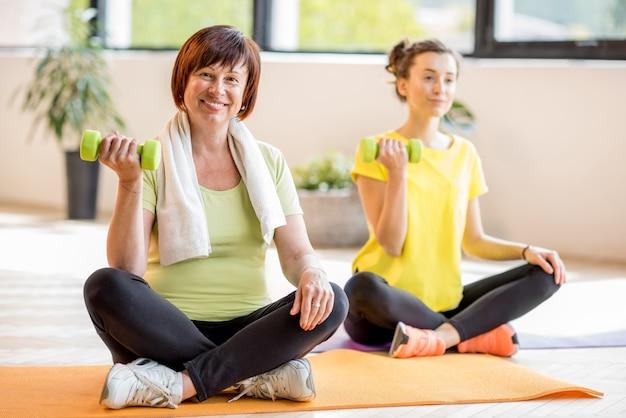 Młoda i starsza kobieta w sporcie nosi siedzącą podczas treningu jogi w pomieszczeniu