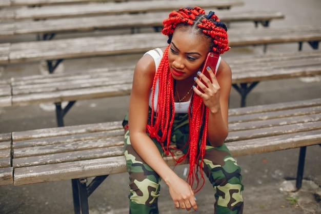 Młoda i stylowa ciemnoskóra dziewczyna z czerwonymi dreadami siedząca w letnim parku