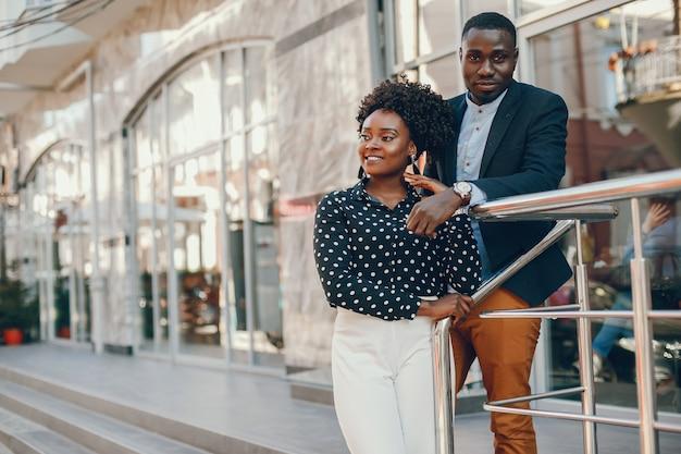 Młoda i stylowa ciemnoskóra para stojąca w słonecznym mieście