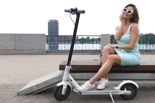 Młoda i stylowa kobieta ze skuterem elektrycznym nad brzegiem rzeki
