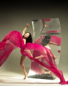 Młoda i stylowa nowoczesna tancerka baletowa na brązie z lustrem