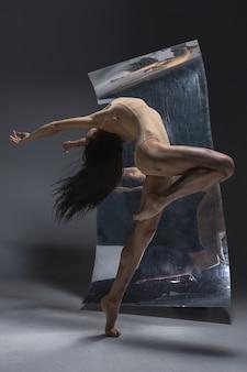 Młoda i stylowa nowoczesna tancerka baletowa na szarej ścianie z lustrem i odbiciami iluzji na powierzchni