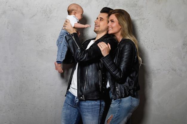 Młoda i stylowa rodzina. szczęśliwa matka i ojciec z małym dzieckiem.