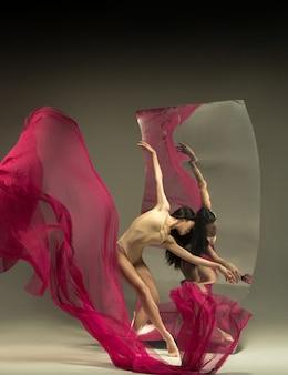 Młoda i stylowa tancerka baletowa przed lustrem