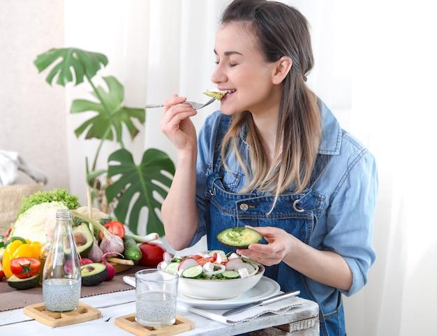 Młoda i szczęśliwa kobieta jedzenie sałatki przy stole
