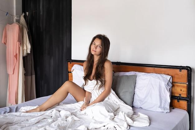 Młoda i szczęśliwa kobieta relaksuje w łóżku