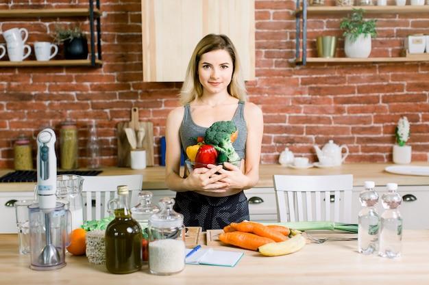 Młoda i szczęśliwa kobieta trzyma szklanego puchar z świeżymi warzywami podczas gdy stojący na stole z zdrowym jedzeniem w nowożytnej kuchni. koncepcja zdrowej żywności