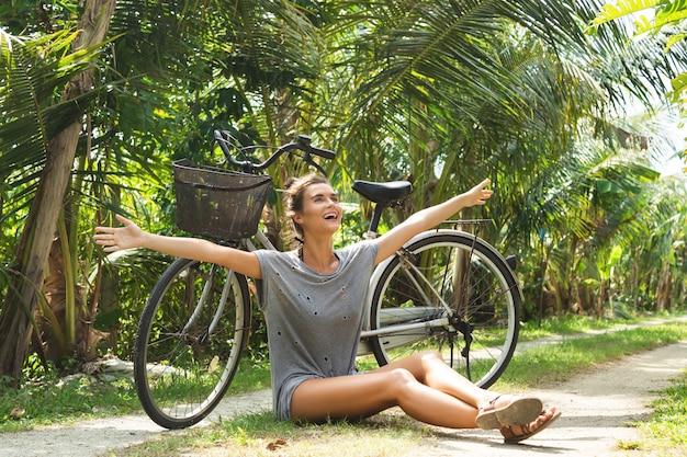Młoda i szczęśliwa kobieta z bicyklem w tropikalnym ogródzie