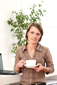 Młoda i szczęśliwa kobieta z filiżanką kawy