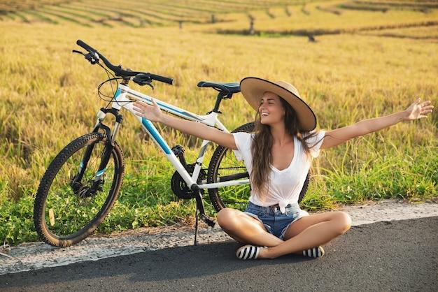 Młoda i szczęśliwa kobieta z rowerem na poboczu drogi