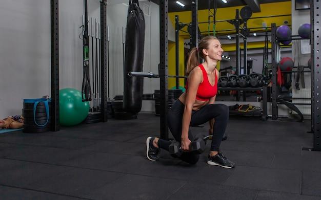 Młoda i szczupła kobieta ćwicząca z hantlami w nowoczesnej siłowni. rzuca z hantlami w dłoni
