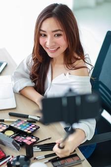 Młoda i urocza azjatycka vlogerka, influencerka lub sprzedawczyni online trzyma smartfon na długim kiju, aby zrobić sobie wideo selfie i transmitować na żywo do recenzji kosmetyków. koncepcja marketingu online.