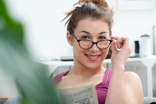 Młoda i uśmiechnięta kobieta w okularach, czytanie gazety