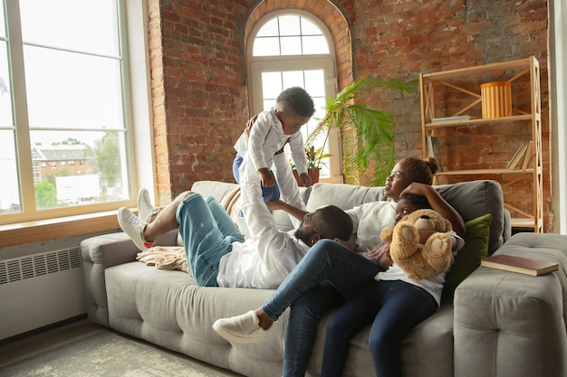 Młoda i wesoła afrykańska rodzina podczas izolacji kwarantannowej spędzająca wspólnie czas w domu