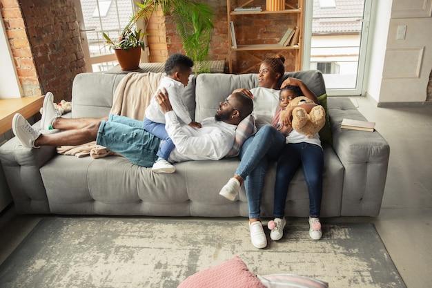 Młoda i wesoła afrykańska rodzina podczas kwarantanny, spędzająca wspólnie czas w domu. pojęcie stylu życia kwarantanny, wspólnoty, komfortu w domu.