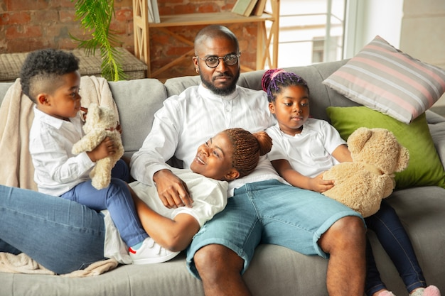 Młoda i wesoła afrykańska rodzina spędzająca razem czas w domu.
