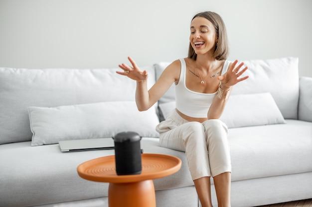 Młoda i wesoła kobieta sterująca urządzeniami domowymi inteligentnym głośnikiem, siedząca na kanapie w domu. inteligentny dom i zarządzanie domem za pomocą koncepcji poleceń głosowych