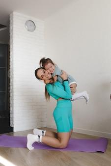 Młoda i wysportowana mama w dresie przytula córkę po wspólnym treningu fitness