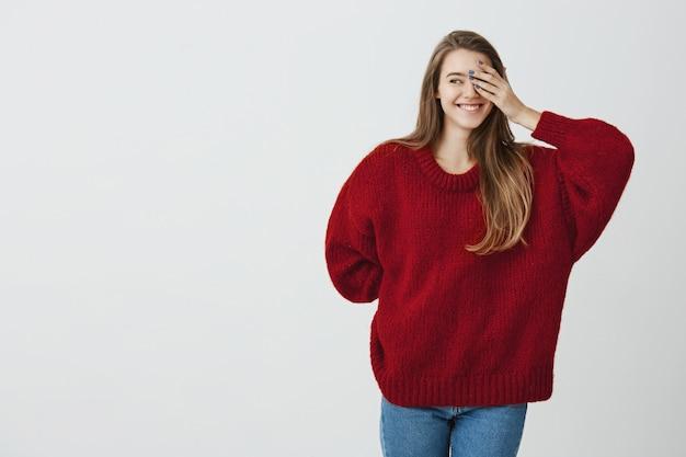 Młoda i zakochana. urocza ładna kobieta w luźnym czerwonym swetrze, chowająca się za dłoń i zakrywająca jedno oko, spoglądająca w lewo i uśmiechająca się wesoło, stojąca