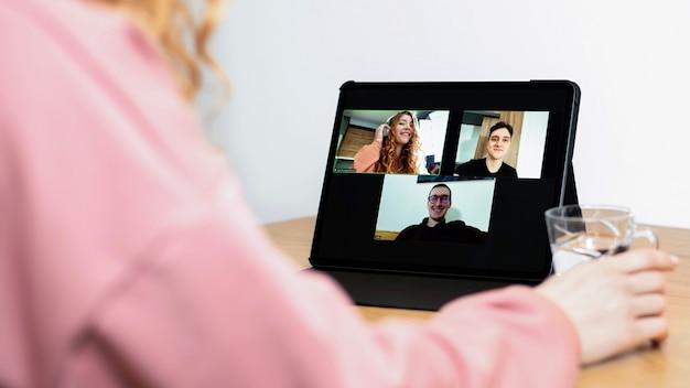 Młoda imbirowa dziewczyna ze słuchawkami rozmawia z przyjaciółmi w wideokonferencji. grupa młodych ludzi pracujących w domu