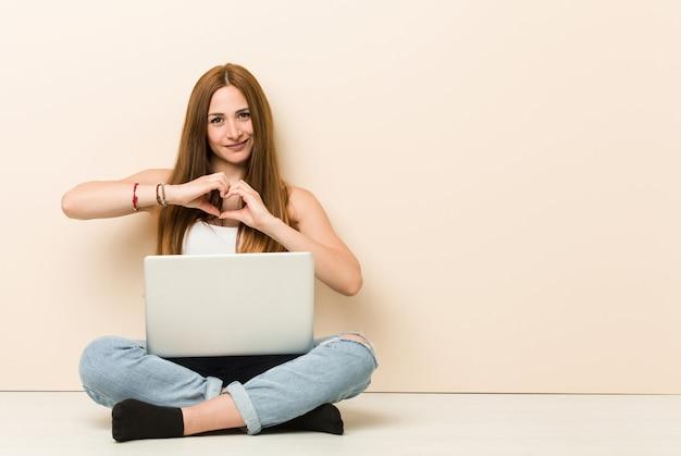 Młoda imbirowa kobieta siedzi na jej domowej podłoga uśmiecha się kształt serca z rękami i pokazuje.