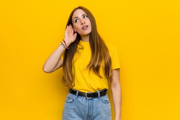 Młoda imbirowa rudzielec kobieta próbuje słuchać plotki.