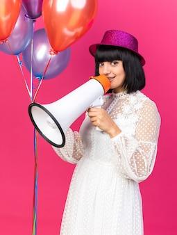 Młoda imprezowa dziewczyna w imprezowym kapeluszu, stojąca w widoku z profilu, trzymająca balony rozmawiające przez głośnika odizolowanego na różowej ścianie