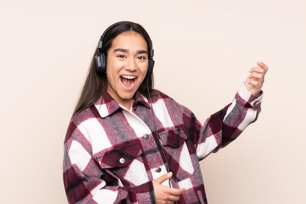 Młoda indianka na beżowej ścianie słuchania muzyki i wykonywania gestu na gitarze