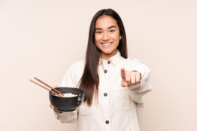 Młoda indianka odizolowana na beżowych punktach palcem na ciebie z pewnym siebie wyrazem, trzymając miskę makaronu pałeczkami