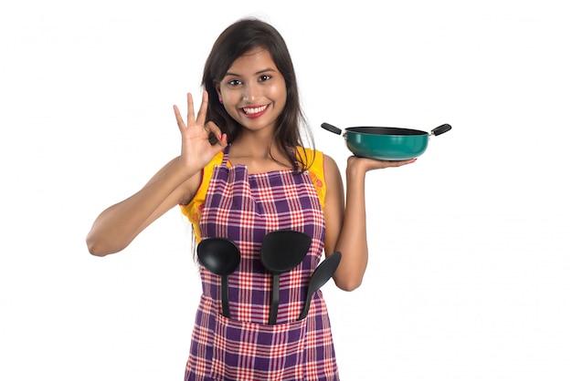 Młoda indianka trzymająca przybory kuchenne (łyżka, zszywka, chochla i patelnia itp.) na białej przestrzeni