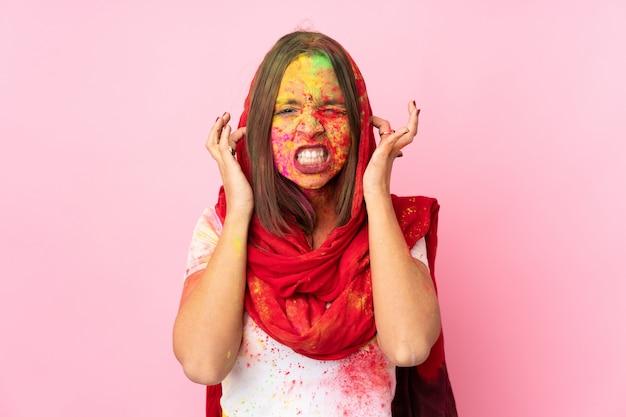 Młoda indianka z kolorowymi pudrami holi na twarzy na różowej ścianie sfrustrowana i zakrywająca uszy