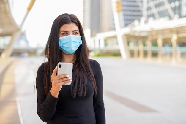 Młoda indianka z maską myśli podczas korzystania z telefonu na moście skywalk