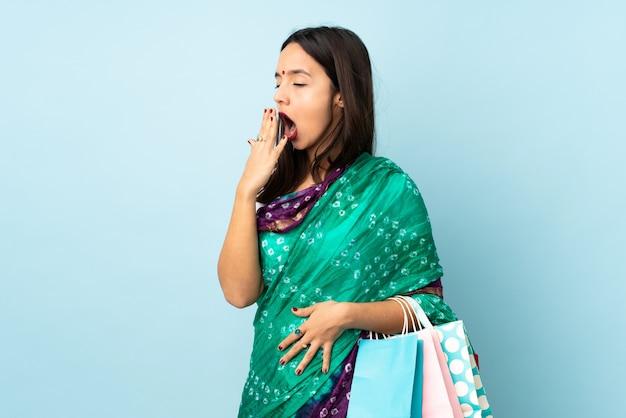 Młoda indianka z torby na zakupy ziewanie i obejmujących szeroko otwarte usta ręką