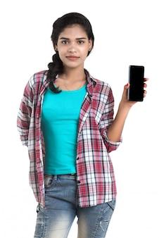 Młoda indiańska dziewczyna używa telefon komórkowego lub smartphone odizolowywających na białej przestrzeni